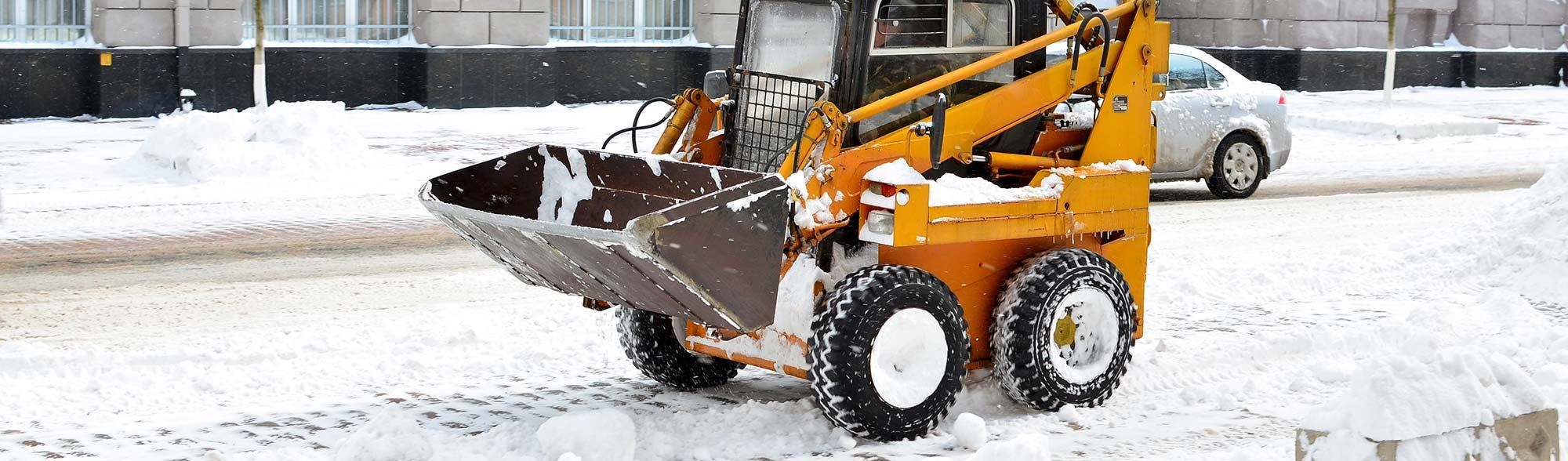 Bobcat removing snow from parking lot